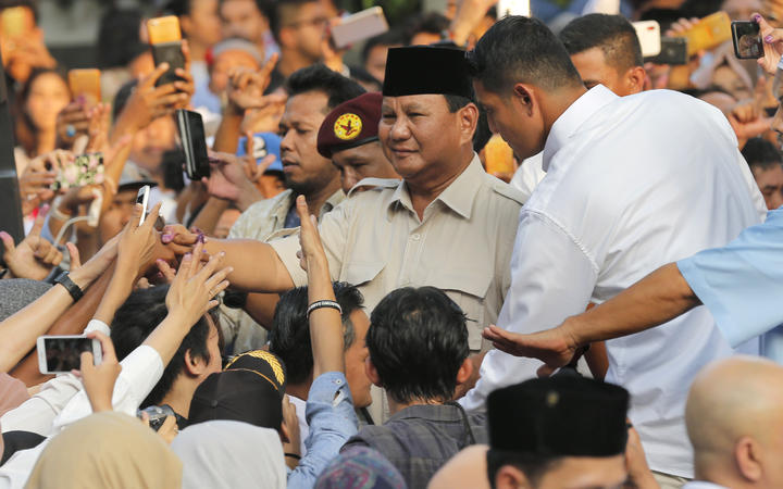 Indonesian presidential candidate Prabowo Subianto, center, shakes hands with his supporter after press conference in Jakarta, Indonesia on 17 April, 2019.