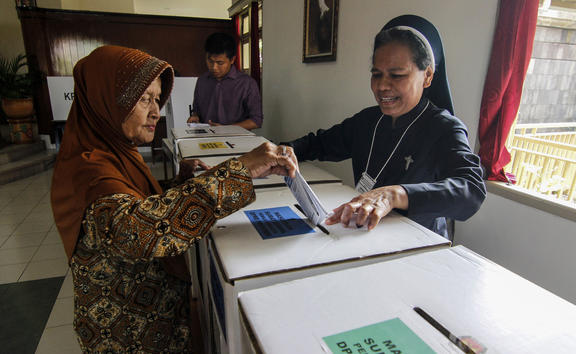A Catholic nun assists an elderly Muslim woman to cast her ballot at a polling station at a convent in Yogyakarta, Indonesia, on 17 April, 2019.