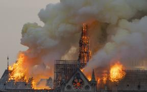 Smoke billows as flames burn through the roof of the Notre Dame de Paris Cathedral