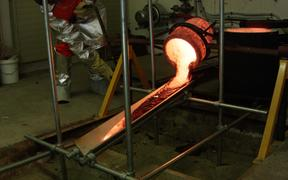 Molten lava pouring out the crucible down the tilted metal plate and beginning to cool down.