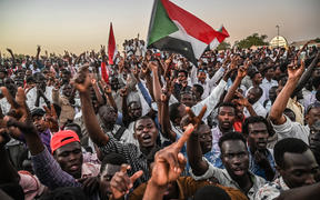Sudanese protesters gather as they shout slogans and wawe national flags during a protest outside the army headquarters in the capital Khartoum on April 21, 2019.