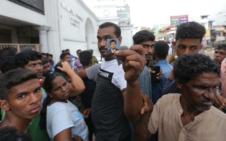 A Sri Lankan catholic devotee holds a blood-stained photograph as people wait to identify dead bodies of their loved ones in front of the St Anthony's Church.