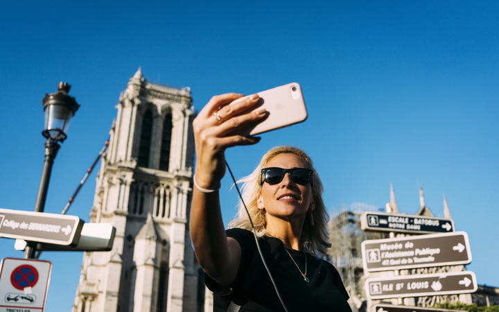 On the first weekend after the fire that devastated Notre-Dame de Paris Cathedral, tourists swarmed in front of the historic monument and took selfies.
