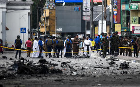 Sri Lankan security personnel inspect the debris of a car after it explodes when police tried to defuse a bomb near St. Anthony's Shrine as priests look on in Colombo on April 22, 2019, a day after the series of bomb blasts targeting churches and luxury hotels in Sri Lanka.