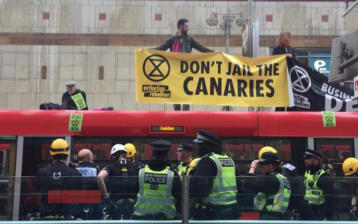Extinction Rebellion protesters on the roof of a train at Canary Wharf, London, 25 April, 2019.