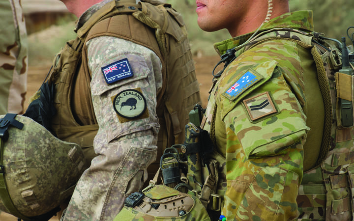 Close up of New Zealand and Australian soldiers side by side in uniform with their country flag on their sleeves.
