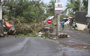 People stand by fallen trees on April 25, 2019 in Moroni after tropical storm Kenneth hit Comoros.