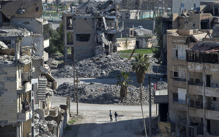 Syrian men walk amidst debris in the Islamic State (Isis) group's former Syrian capital of Raqqa.