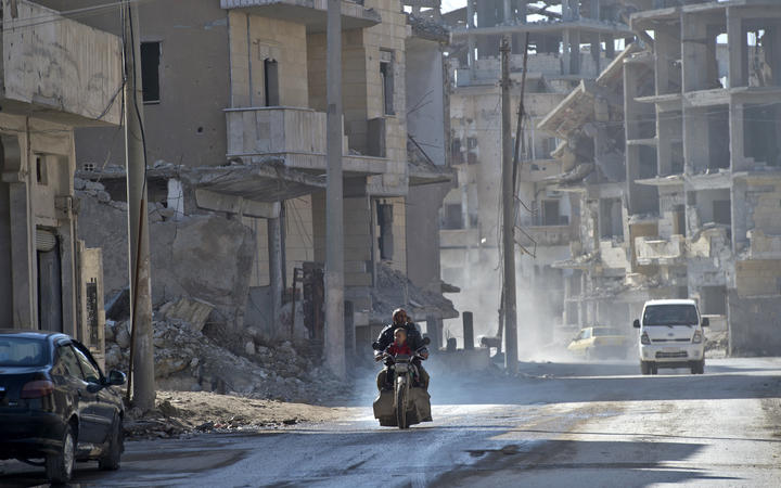 A Syrian man and a child ride a motorcycle in the Islamic State (Isis) group's former Syrian capital of Raqqa.