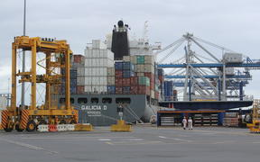 Cranes and container movers work to laod a ship at the Ports of Auckland