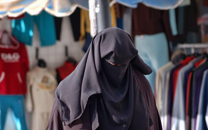 21293717 - woman in a burqa on the streets of egypt