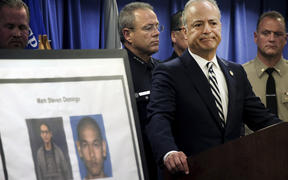 US Attorney Nick Hanna stands next to photos of Mark Steven Domingo during a news conference.