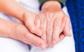 Carer giving helping hands for elderly woman.