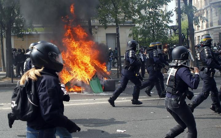 Police officers pass by burning garbage as they confront demonstrators during a May Day rally in Paris.