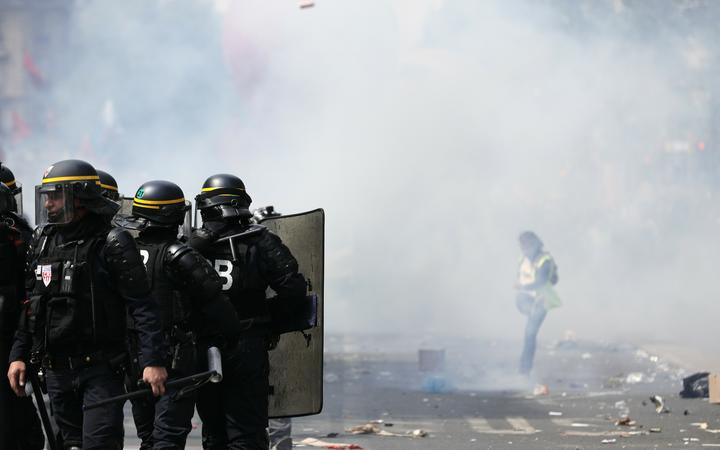A protestor kicks away a tear gas canister during the protest.