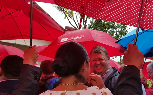 The Labour Party delegation lines up at the gate of the marae at Waitangi, amid a sea of red umbrellas.