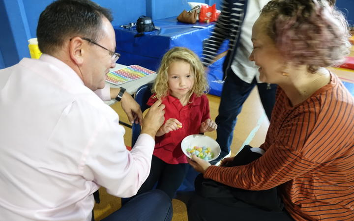 Whangarei National MP Shane Reti vaccinated 6 yr old Pippa Howie at Hikurangi School while mum Alysha looks on.