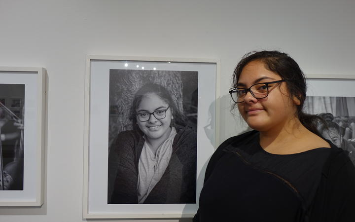 Willow Tuliakiono next to her photo which is part of the Virtuoso Strings photo exhibition.