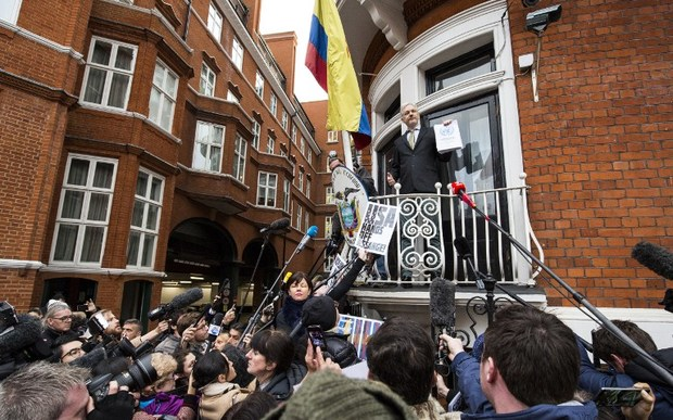 Julian Assange (centre) addresses media and supporters from the balcony of Ecuador's embassy.