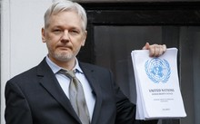 Wikileaks founder Julian Assange speaks from the balcony of the Ecuadorian embassy, holding up the UN Panel's decision.