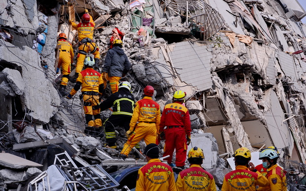 Rescuers try to look for victims at the site where a building collapsed during an earthquake in Tainan.