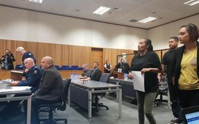 Ani Nohinohi and her supporters approach the witness stand.
