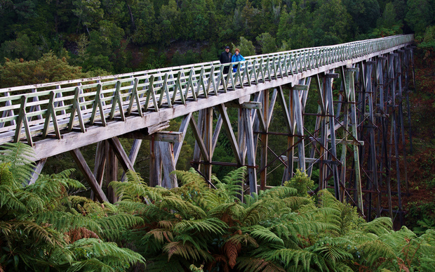A pair of walkers cross the Percy Burn Viaduct on the South Coast Track near Tuatapere.