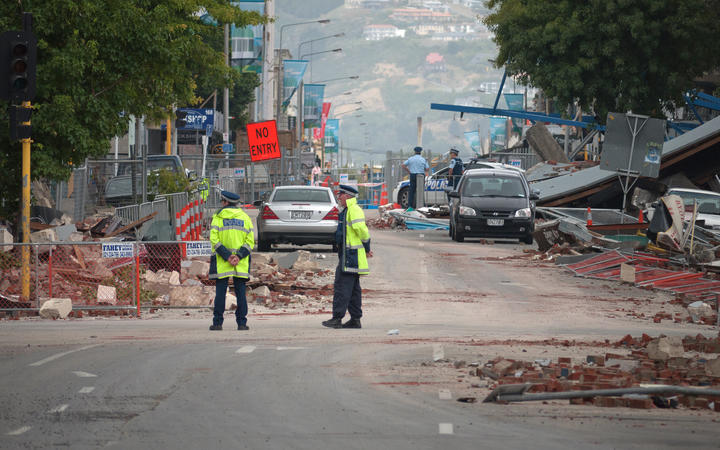 Police stand by amid fallen debris in a cordoned-off street in Christchurch on February 23, 2011 a day after the deadly earthquake.