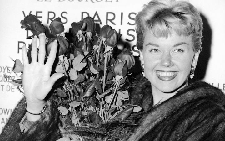 American actress and singer Doris Day holds a bouquet of roses at Le Bourget Airport in Paris in 1955 after flying in from London.