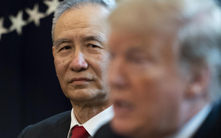 China's Vice Premier Liu He looks on as US President Donald Trump speaks.