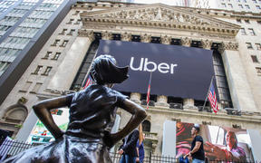 An Uber banner adorns the facade of the New York Stock Exchange ahead of the ride sharing company's IPO.