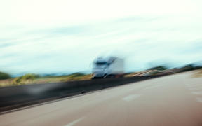 Conceptual silhouette of a defocused truck in motion on highway - pov of driver under alcohol or narcotic substance