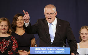 Australian Prime Minister Scott Morrison speaks to party supporters flanked by his wife, Jenny, second left, and daughters Lily, right, and Abbey, after his opponent conceded in the federal election in Sydney, Australia.