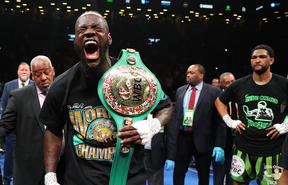 Deontay Wilder celebrates after his first round knockout of Dominic Breazeale who looks on from the right.
