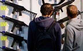 (FILES) In this file photo taken on March 29, 2019, visitors look at semi-automatic shotguns displayed on a wall during the 45th edition of the Arms Trade Fair, in Lucerne.