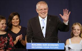 Australian Prime Minister Scott Morrison, second right, speaks to party supporters flanked by his wife, Jenny, second left, and daughters Lily, right, and Abbey, after his opponent concedes in the federal election in Sydney, Australia, Sunday, May 19, 2019.