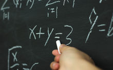 A teacher uses a blackboard to solve a mathematics equation.