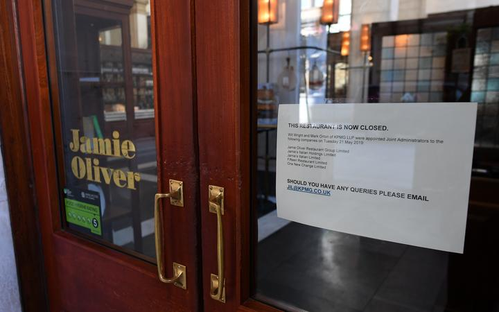 A sign in the door announcing the closure of a Jamie Oliver restaurant in Manchester, 21 May 2019.