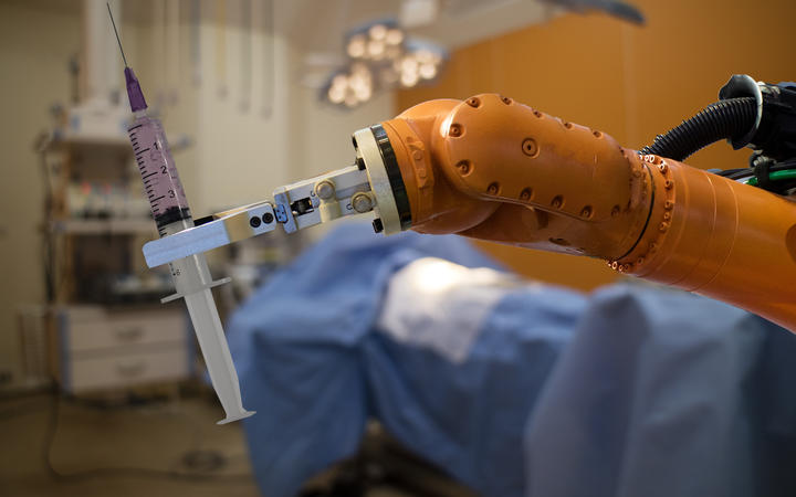 robot in medical concept, robot (artificial intelligence)hold the medical syringe in the operating room  for prepare to surgery the patient for faster recovery time, less cosmetic damage and low costs