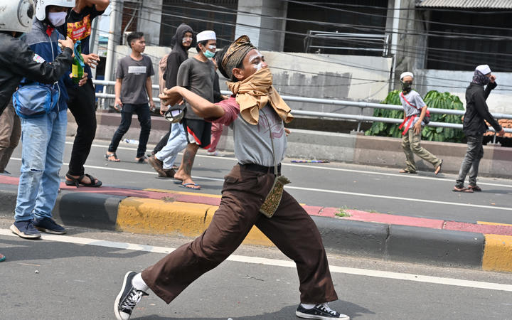 Protesters hurl rocks toward police during a clash in Jakarta.