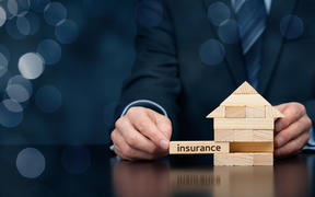 Property (family house) insurance protection concept. Insurance agent complete wooden model of the house with last piece with text insurance. Wide banner composition with bokeh background.