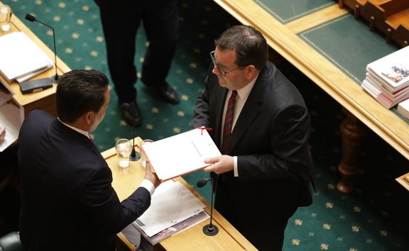 Finance Minister Grant Robertson hands the Budget Speech to National Party leader Simon Bridges.