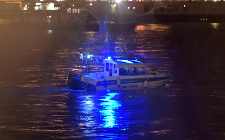 Crew-members of a police boat search for survivors after a riverboat capsized on the Danube River in Budapest.