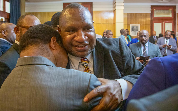 James Marape (right) is hugged by a supporter.