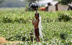 (FILES) In this file photo taken on May 29, 2019, an Indian boy pours water on himself as he tries to cool himself off amid rising temperatures in New Delhi. -