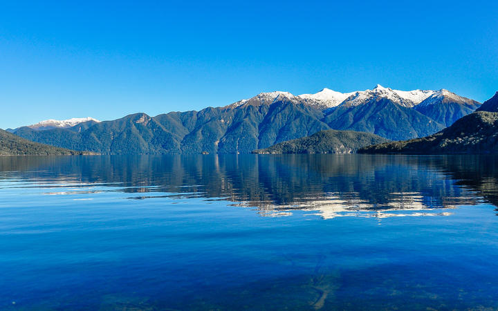 Reflection of snowy mountains in Lake Hauroko in the Southern Scenic Route, New Zealand