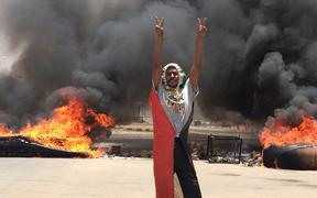 A protester in front of burning tires and debris on the road near Khartoum's army headquarters.
