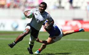 Fiji's Jerry Tuwai breaks through the France defence in Paris.