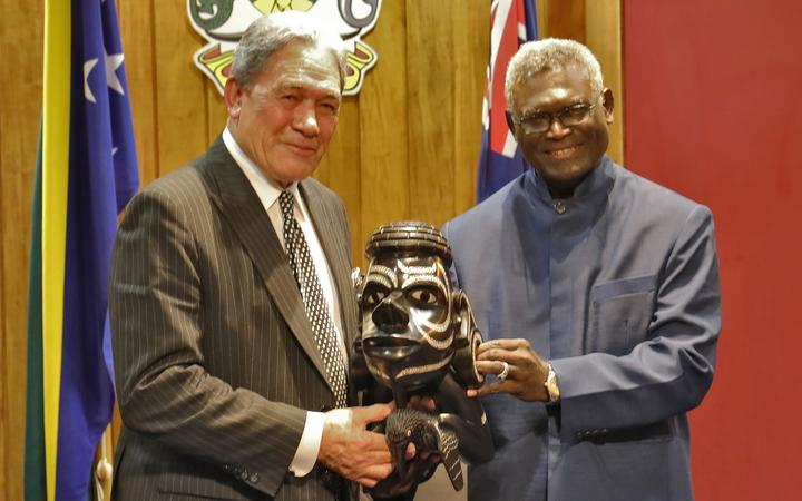 Solomon Islands prime minister (right) Manasseh Sogavare presents a Nguzu Nguzu to New Zealand's deputy prime minister Winston Peters. June 2019