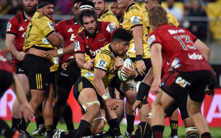 Kane Le'aupepe looks on in the background on his Super Rugby debut as Ardie Savea is tackled by Sam Whitelock.